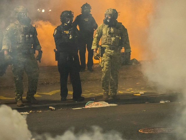 PORTLAND, OR - JULY 21: Federal police walk through tear gas while dispersing a crowd of about a thousand protesters at the Mark O. Hatfield U.S. Courthouse on July 21, 2020 in Portland, Oregon. The federal police response to the ongoing protests against racial inequality has been criticized by city …