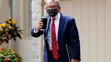 Ohio Gov. Mike DeWine acknowledges members of the media while entering his residence after testing positive for COVID-19 earlier in the day Thursday, Aug. 6, 2020, in Bexley, Ohio. DeWine tested positive using a rapid test Thursday, before testing negative later in the day using a more sensitive laboratory-developed test. …