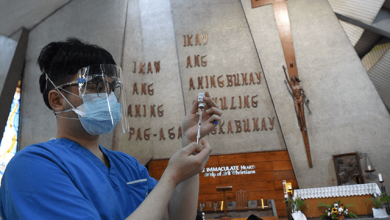 A health worker (L) prepares to inoculate residents with a dose of the AstraZeneca/Oxford's Covid-19 coronavirus vaccine inside a Catholic church turned into a vaccination centre in Manila on May 21, 2021. (Photo by TED ALJIBE / AFP) (Photo by TED ALJIBE/AFP via Getty Images)